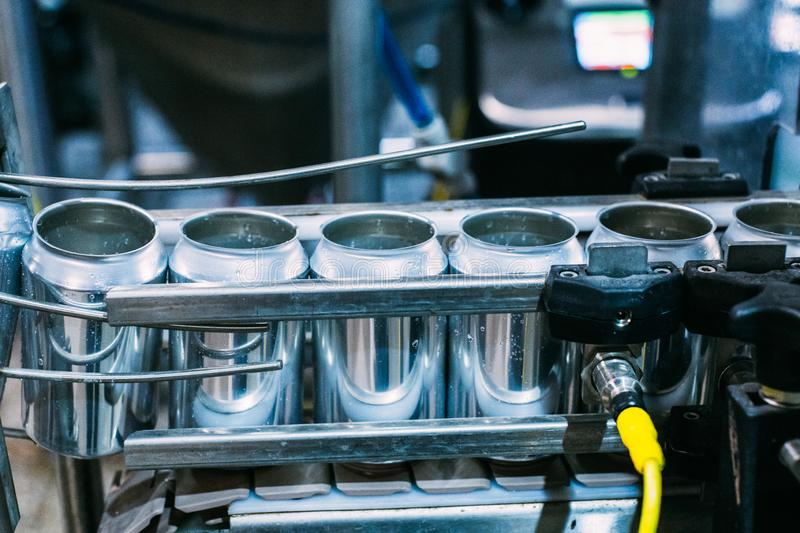 Transportation of aluminum cans on the conveyor for bottling beer .Brewery for the production. stock photography