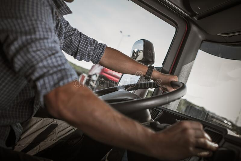 Trucker Behind the Wheel. Transportation and Automotive Industry. Commercial Driving. Caucasian Truck Behind the Wheel stock photo