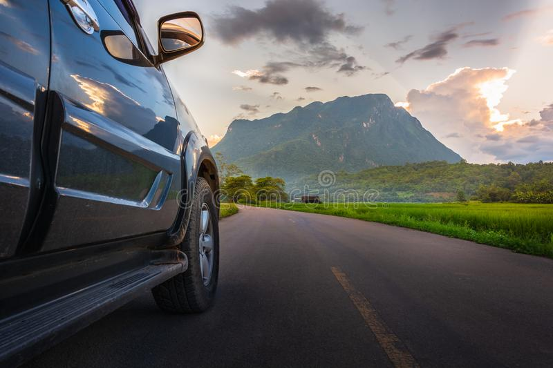 Transportation and car journey concept with SUV car on road and. Sunset, mountain background stock photo