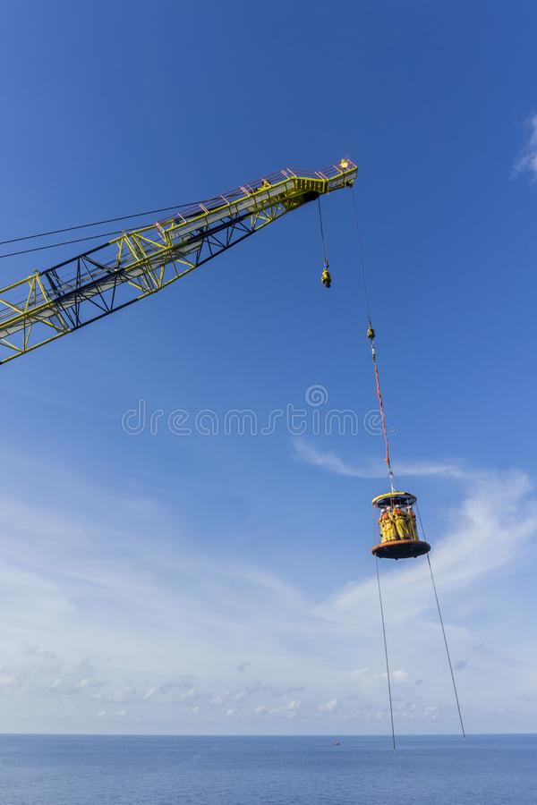 Oil and Gas Industrial. Transportation. A group of offshore crew crossing the sea from Accommodation Work Barge (AWB) to oil and gas platform using Personal royalty free stock photography