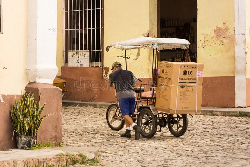 Transportation of a modern washing machine with a bicycle in Trinidad, Cuba. stock photography