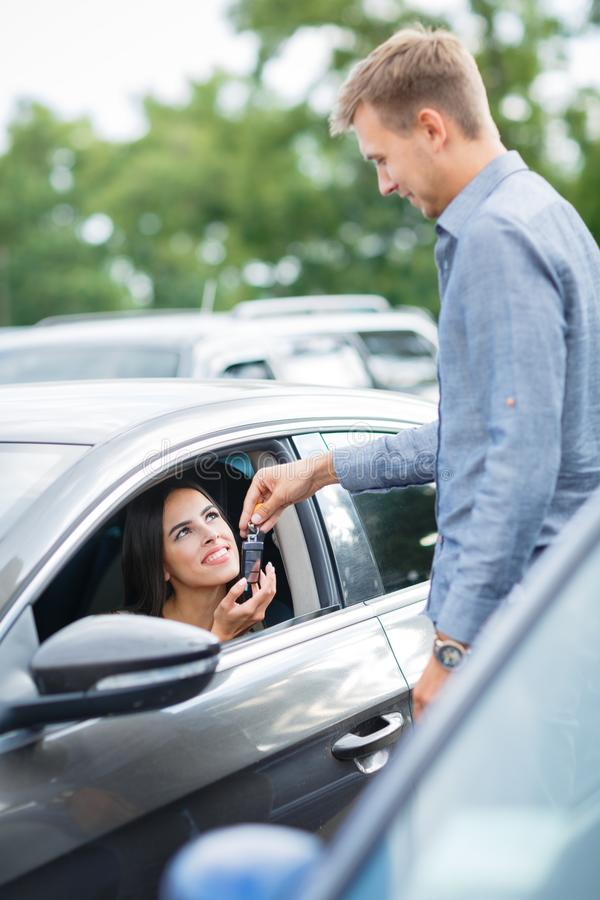 Cropped view of man in car dealership giving car keys to client. Transportation and ownership concept - customer and salesman with car key outside royalty free stock photos