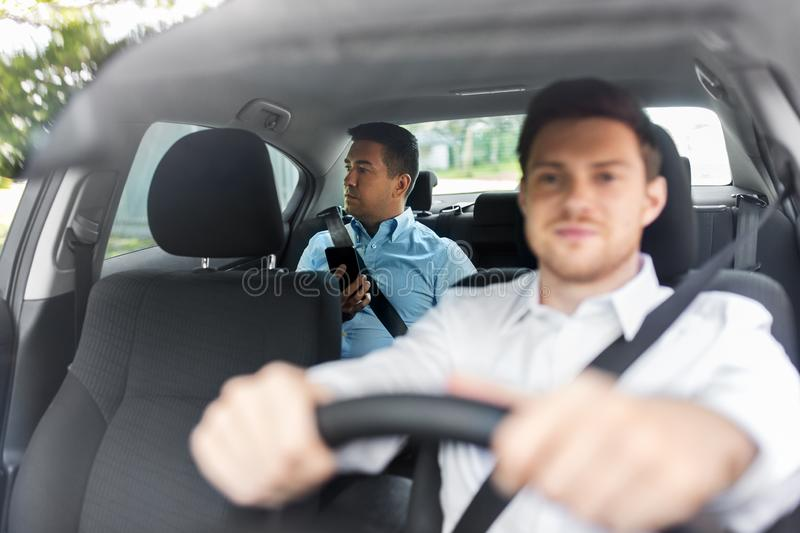 Male passenger with smartphone and car driver. Transportation, vehicle and people concept - middle aged male passenger with smartphone on back seat and car royalty free stock photo