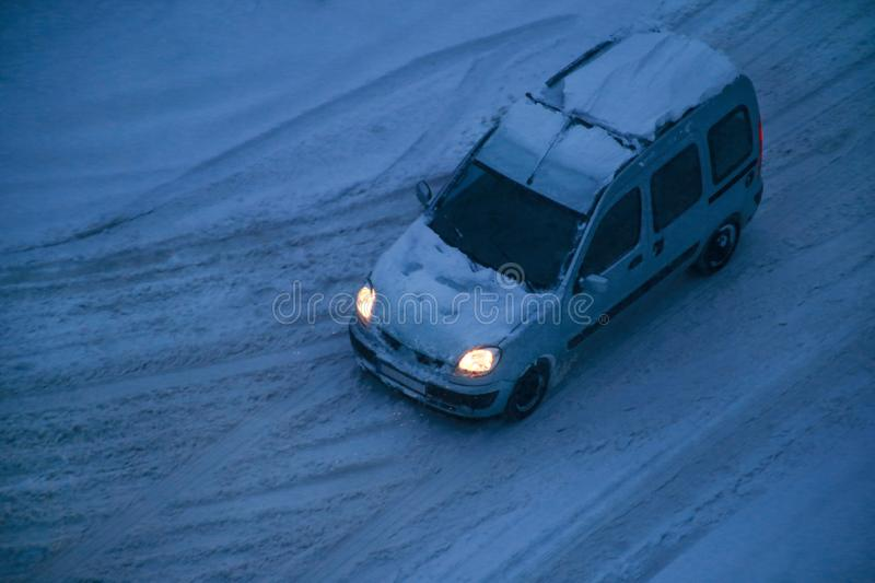 Transportation, winter season. Car moving covered in snow after blizzard and road street. View of winter, snowing on city street. royalty free stock image