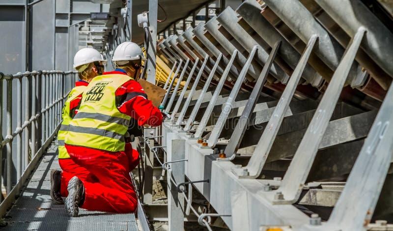 Transportband die Platinaerts voor verwerking met veiligheid in de mijneninspecteurs vervoeren die schade controleren royalty-vrije stock afbeelding