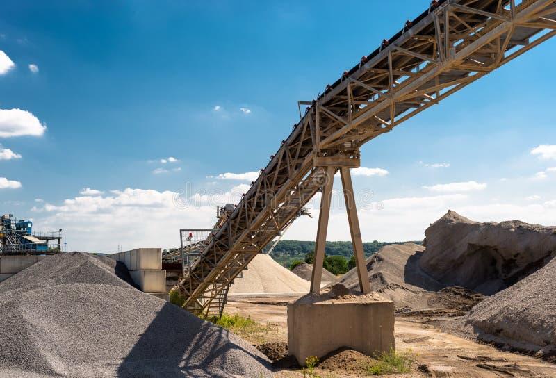 Transportband over hopen van grint op blauwe hemel bij een industriële cementinstallatie stock afbeelding