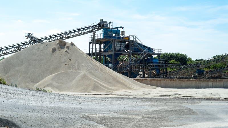Transportband over hopen van grint op blauwe hemel bij een industriële cementinstallatie stock foto