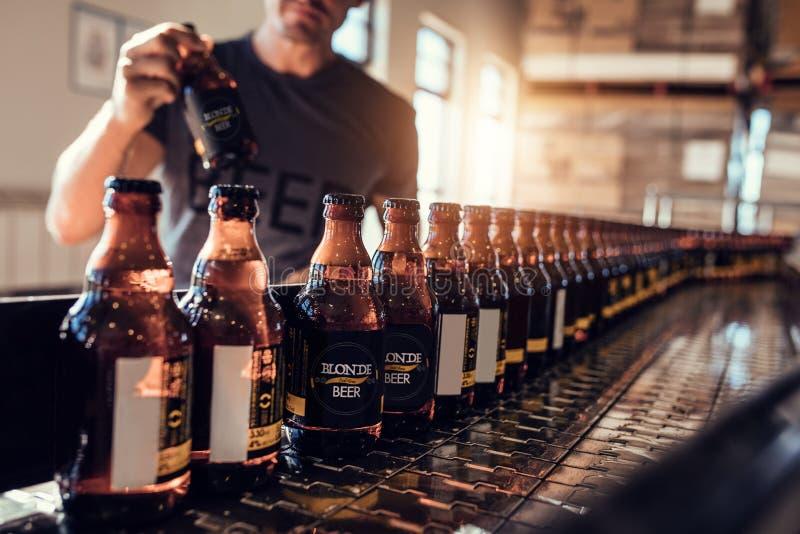 Transporte com as garrafas de cerveja que movem-se na fábrica da cervejaria imagens de stock