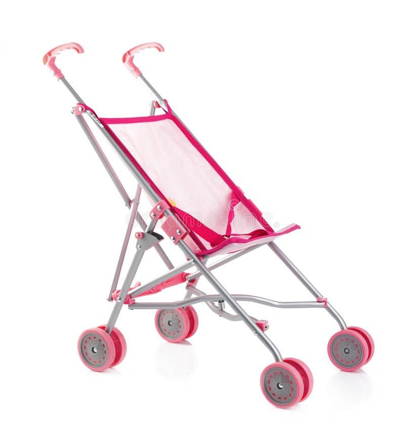 Transporte de bebê ou carrinho de criança cor-de-rosa pequeno da boneca isolado no branco fotos de stock