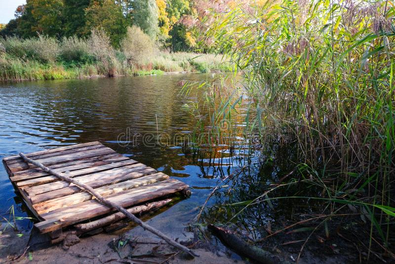 Transporte en balsa en el agua en el otoño en un lago del bosque foto de archivo libre de regalías