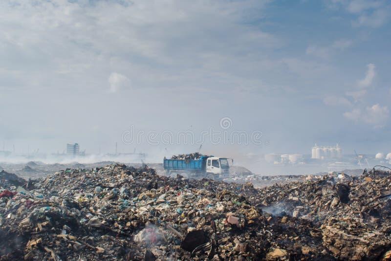 Transporte a equitação na descarga de lixo completamente do fumo, da maca, de garrafas plásticas, de desperdícios e de lixo na il imagem de stock royalty free