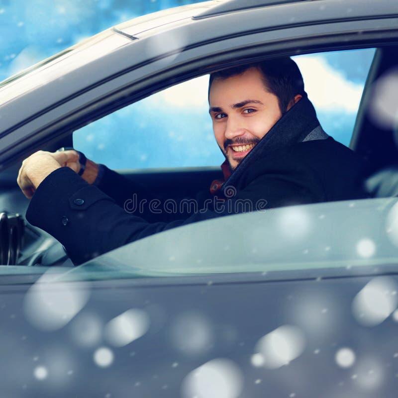 Transporte, invierno y concepto de la gente - conductor sonriente feliz del hombre detrás de la rueda su coche imagen de archivo