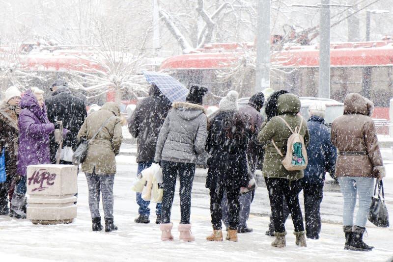 Transporte público de espera dos povos na parada do ônibus no blizzard pesado no inverno fotografia de stock