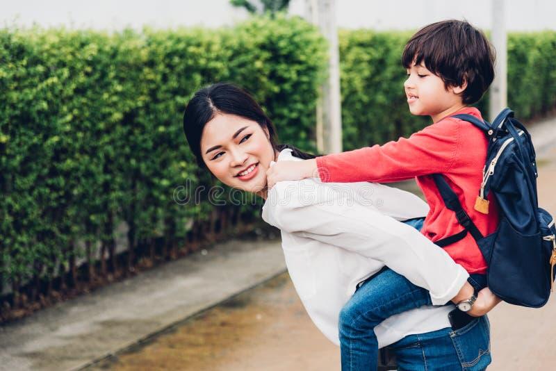 Transporte por ferrocarril asiático del niño en madre al aire libre, él feliz fotos de archivo