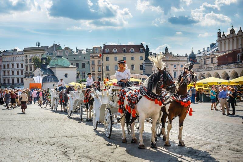 Transporte puxado por cavalos antes do Sukiennice no mercado principal em Krakow, Polônia fotos de stock