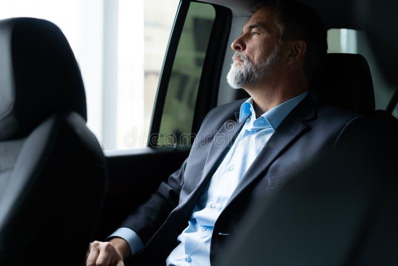 Transporte, viagem de neg?cios e conceito dos povos - homem de neg?cios superior que conduz no banco traseiro do carro fotos de stock royalty free