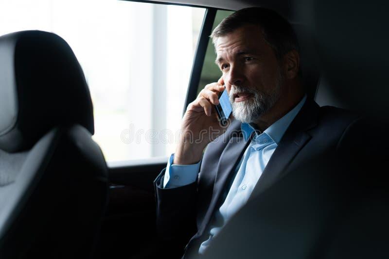 Transporte, viaje de negocios y concepto de la gente - hombre de negocios mayor que conduce en asiento trasero del coche imagenes de archivo
