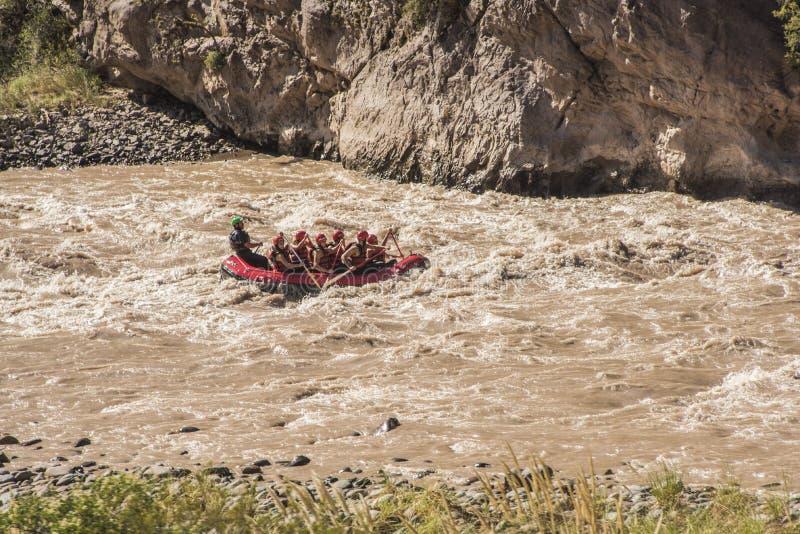 Transporter dans par radeau un torrent créé par les eaux de fonte des neige andines photographie stock