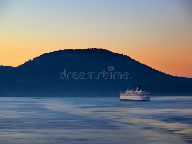 Transportez en bac faire sa manière par l'île au temps de coucher du soleil photographie stock