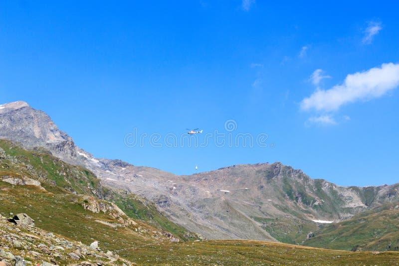 Transportez le vol d'hélicoptère avec des approvisionnements et le panorama de montagne, Alpes de Hohe Tauern, Autriche image stock