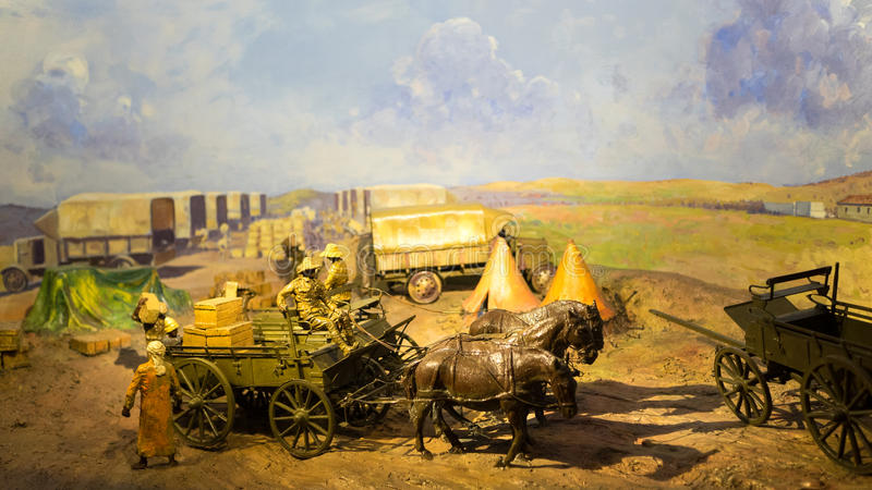 Transporting military supplies. During the earlier world war. The miniature models display men loading cargo to horse carriages royalty free stock image