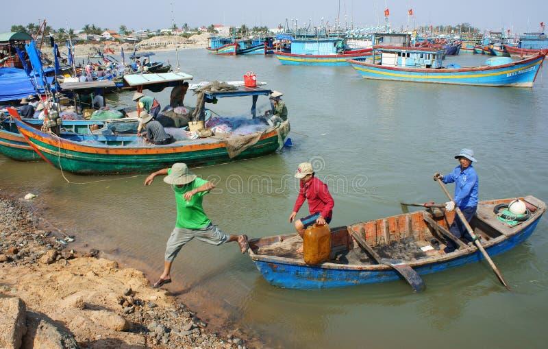 Transportleute und -waren durch hölzernes Boot am habor stockfotografie