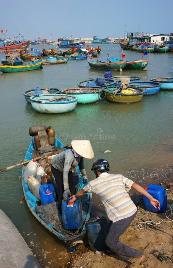 Transportleute und -waren durch hölzernes Boot am habor lizenzfreie stockfotos