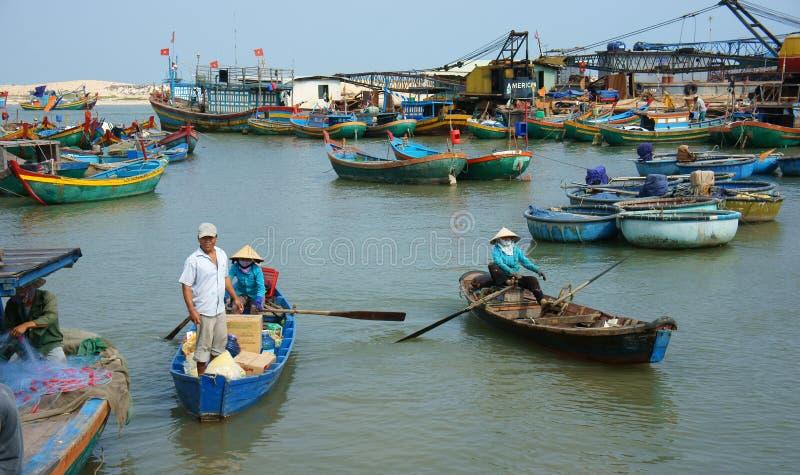 Transportleute und -waren durch hölzernes Boot am habor stockbilder