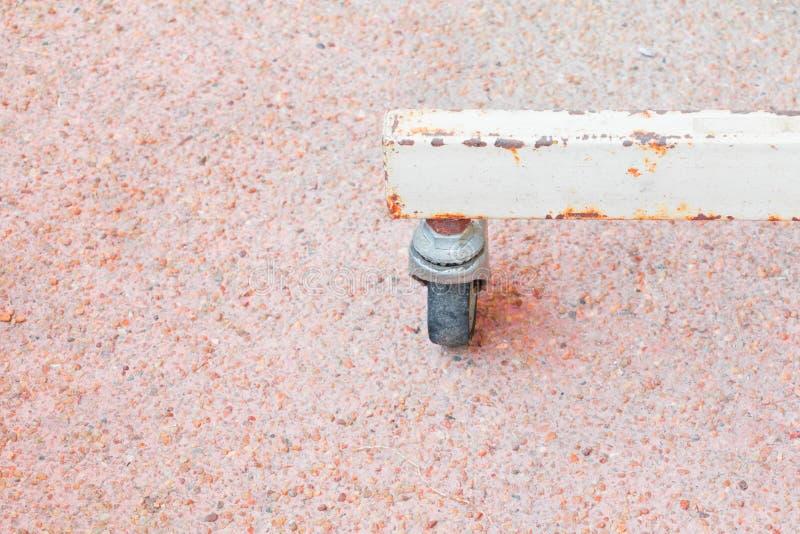 Transportmetall des schwarzen Gummirades rostiges altes kleines Metallauf Bodensandstein stockfoto