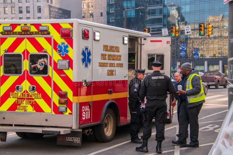 Transportpolisen för två Philadelphia ses av en ambulans för medicinsk service för Philadelphia brandstationnödläge på en stad arkivbild