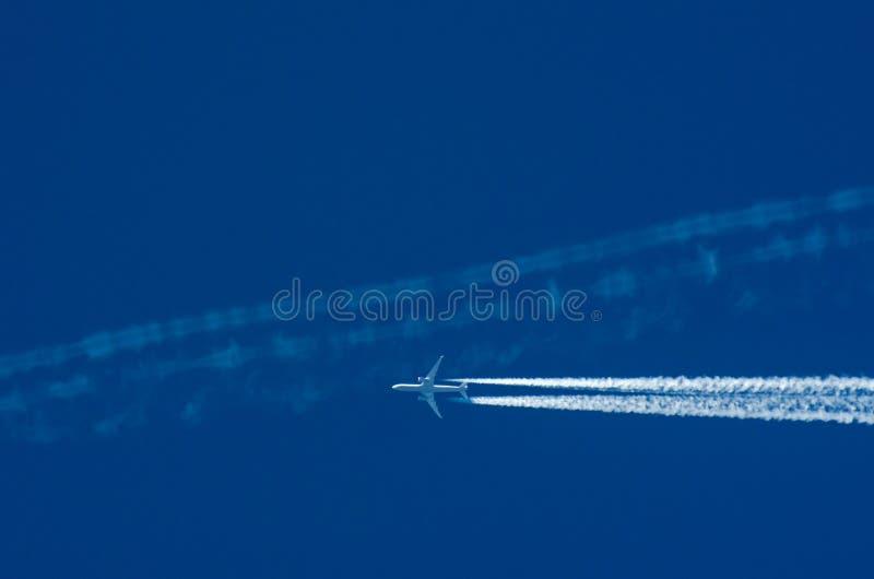 Transportwettbewerbskonzept: ein Jet-Flugzeug, das anderen plane's weißen Contrail gegen Hintergrund des blauen Himmels kreuzt stockfotografie