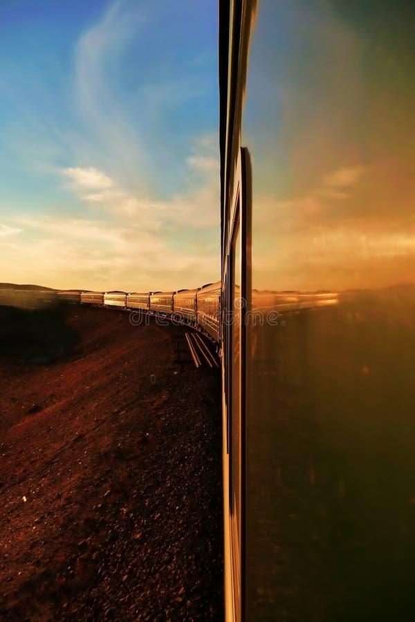 Transsiberische spoorweg: snak trein makend zijn manier door de woestijn in Mongolië bij zonsondergang, zoals die van het achterv royalty-vrije stock afbeeldingen