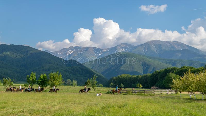 TRANSYLVANIA REGION, ROMANIA - 6 JUNE, 2017: A mountain view i with some horses and riders in a picturesque area royalty free stock photos