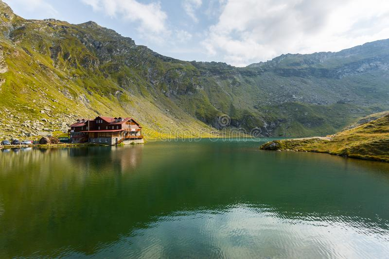 Transylvania, Romania, Europe. House by the green lake with high mountains and cloudy sky. Transylvania, Romania, Europe stock photo