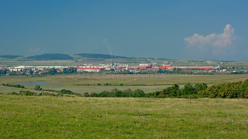 Transylvanian coloca con la ciudad, los edificios industriales y las montañas en el fondo foto de archivo libre de regalías