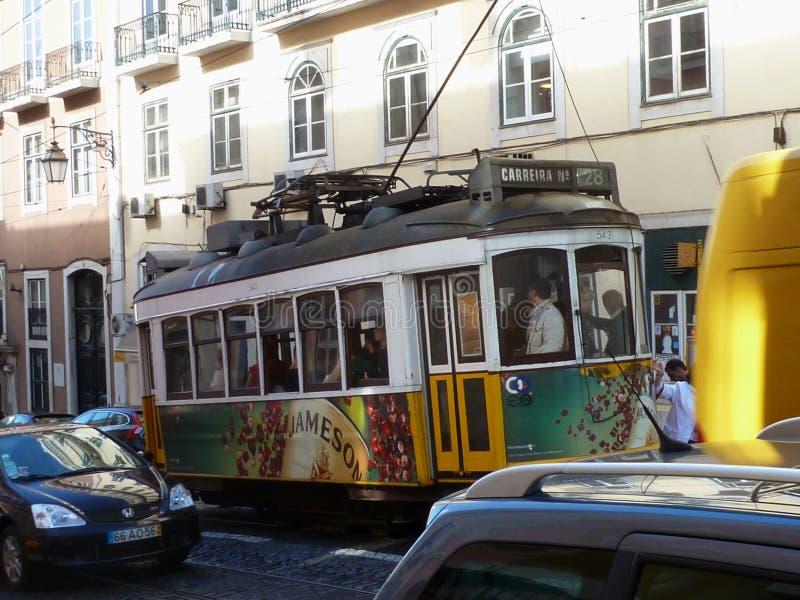 Tranvía amarilla del solo coche de no 28 en Lisboa con tráfico de la calle imagen de archivo libre de regalías