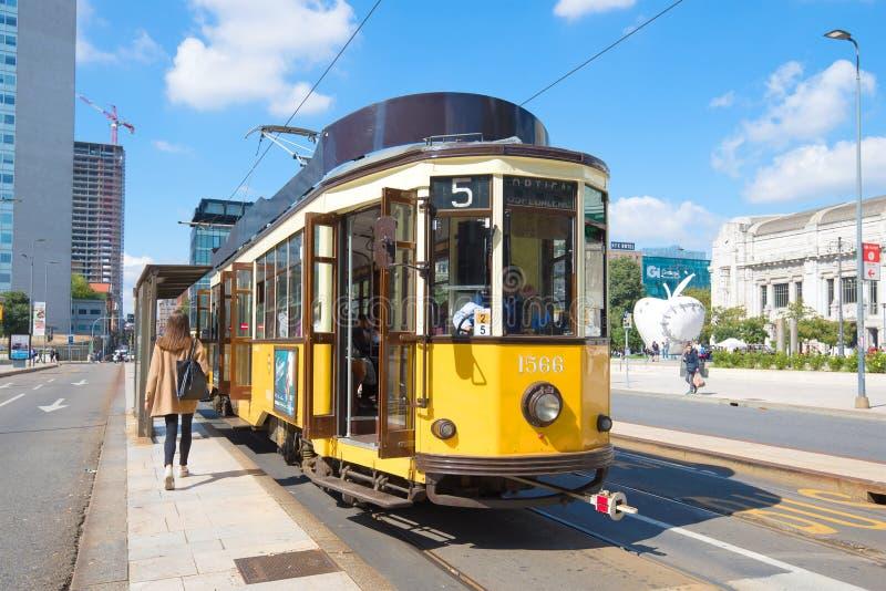 Tranvía amarilla del vintage en una parada del transporte público en el día soleado Milán, Italia fotografía de archivo