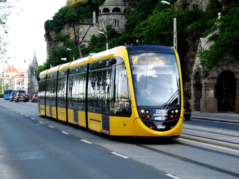 Tranvía amarilla en una calle de Budapest con la torre y la torrecilla de piedra detrás fotos de archivo libres de regalías