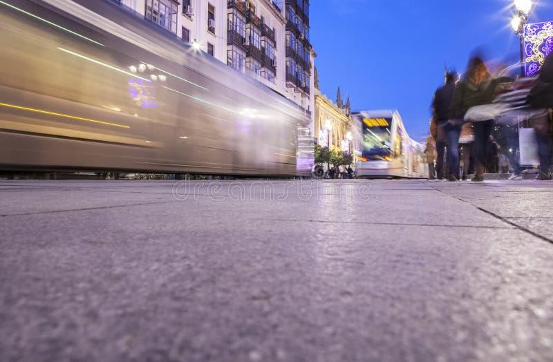 Tranvía que corre adelante en el centro de la ciudad en la noche con la decoración de la Navidad imagen de archivo