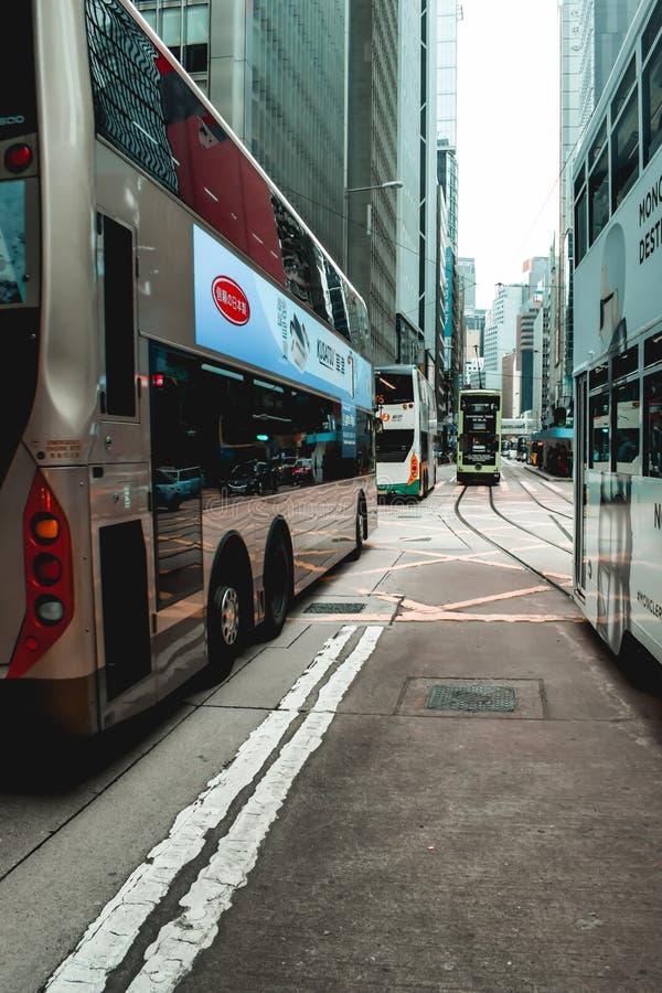 Tranvías y autobuses del autobús de dos pisos que cruzan las calles de Hong Kong imagen de archivo