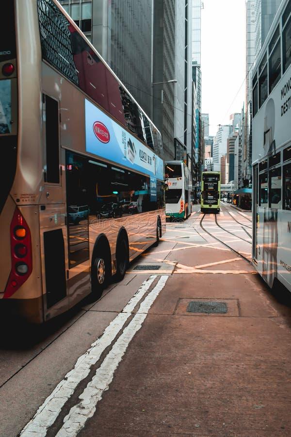 Tranvías y autobuses del autobús de dos pisos que cruzan las calles de Hong Kong fotografía de archivo libre de regalías