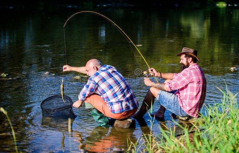 Trap for fish. Men sit at riverside with fishing equipment. Illegal hunting caviar. Extracts eggs from sturgeon caught. River. Poaching crime and fishing stock images