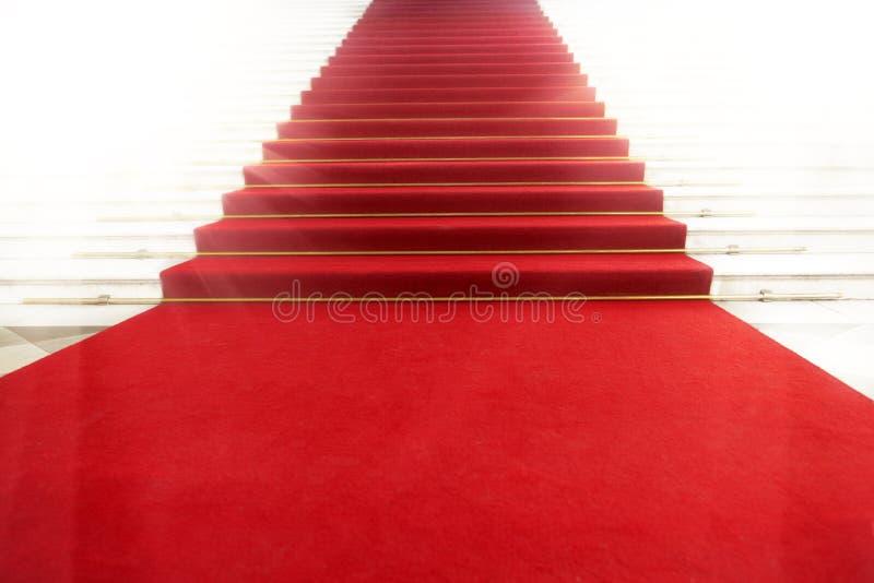 Trap met rood tapijt, dat door licht wordt verlicht
