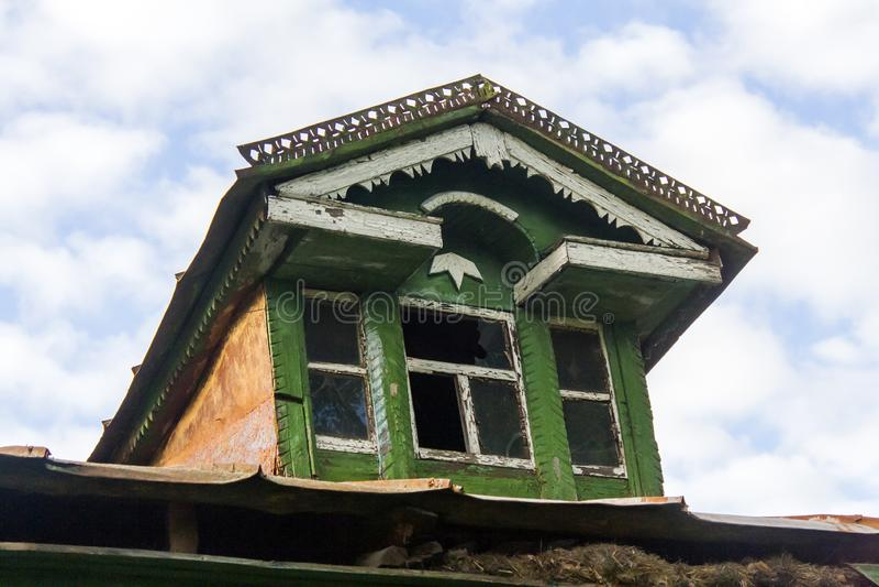 Trapeira-janela decrépita no telhado de uma cabana de madeira do russo imagens de stock