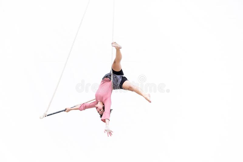 Trapeze artist hung upside down during her performance. MEXICO CITY - NOV 18, 2018: Young girl performs the acrobatic elements in the air trapeze on a white royalty free stock photo
