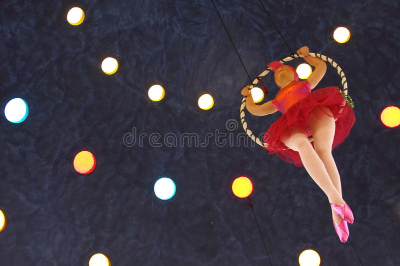 Trapeze doll. A colorful doll is sit in a trapeze against a blue ceiling royalty free stock image