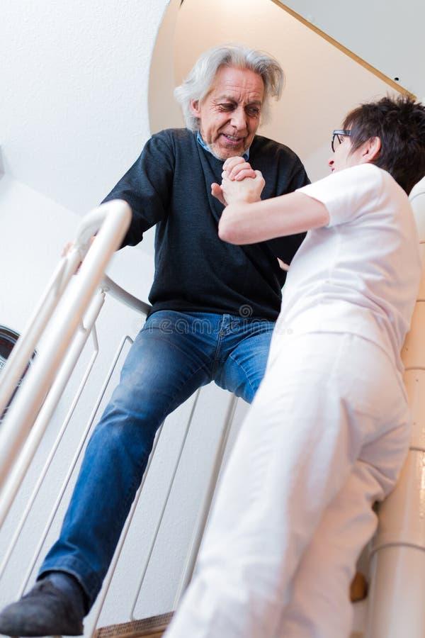 Trappa för sjuksköterskaHelping Senior Man klättring fotografering för bildbyråer
