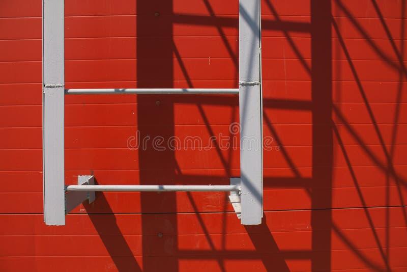 Trappa på den röda väggen Skuggan av trappan royaltyfri foto