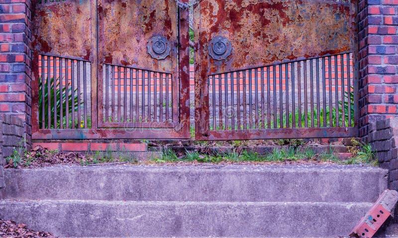 Trappa som leder till den stängda rostade porten arkivbild