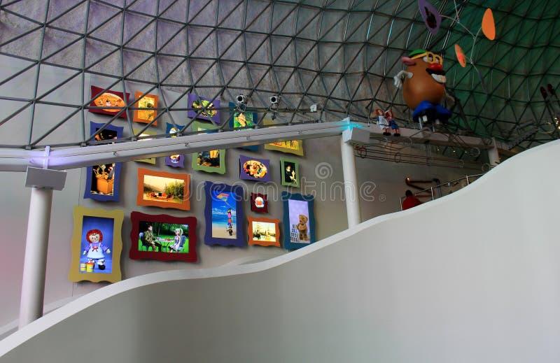 Trappa som upp till leder andra rum, med sikt av leksaker som inramas på väggarna, det starka museet, Rochester, New York, 2017 royaltyfri bild